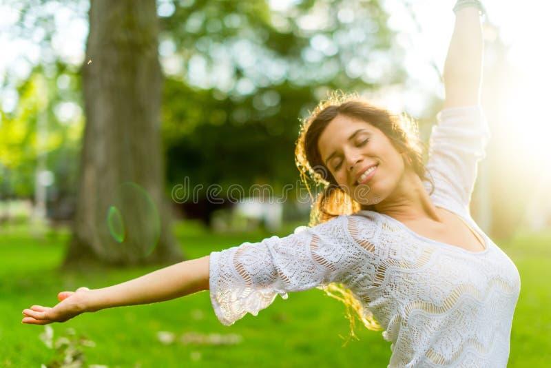 Mång--person som tillhör en etnisk minoritet flicka som tycker om värmen av en solnedgång royaltyfria bilder