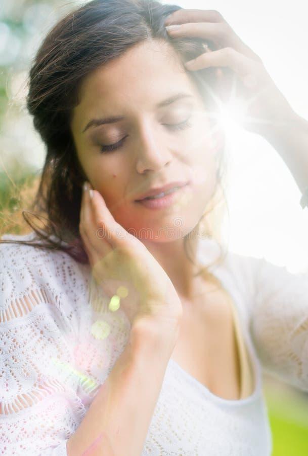 Mång--person som tillhör en etnisk minoritet flicka som tycker om värmen av en solnedgång royaltyfria foton