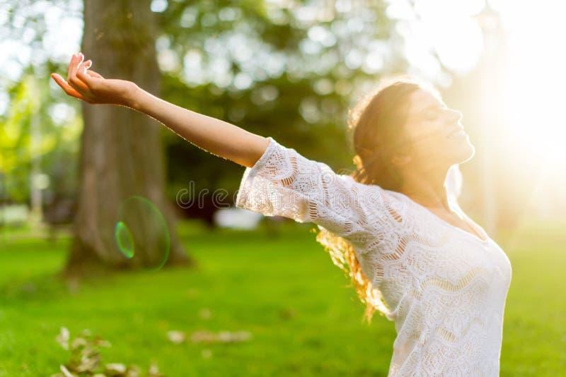 Mång--person som tillhör en etnisk minoritet flicka som tycker om värmen av en solnedgång royaltyfri bild