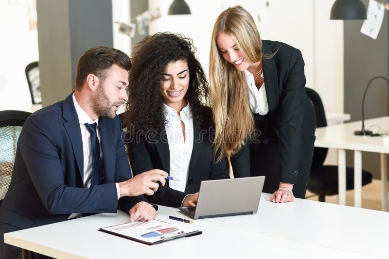 Mång--person som tillhör en etnisk minoritet grupp av tre businesspeople som möter i en modern nolla royaltyfria foton