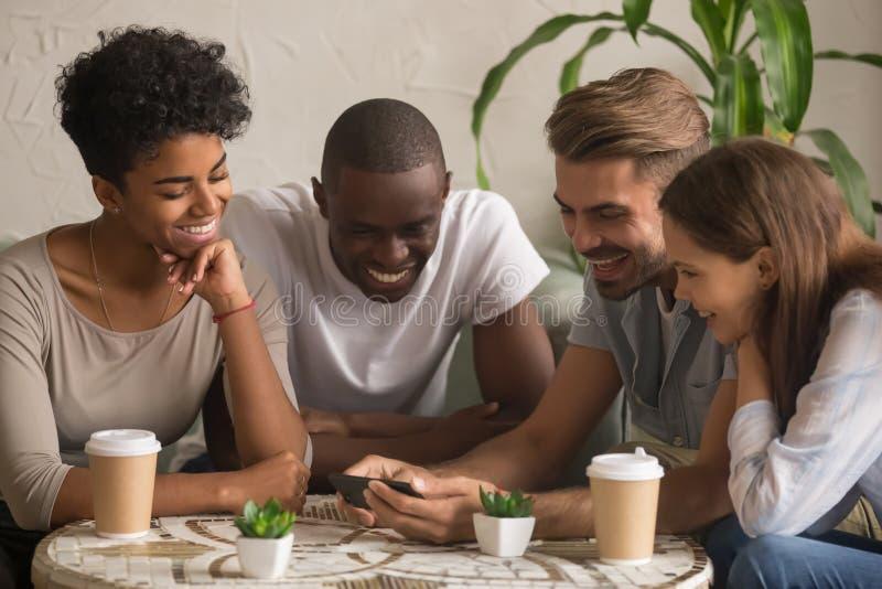 Mång--person som tillhör en etnisk minoritet lyckliga vänner som skrattar den hållande ögonen på roliga mobila videoen på smartph royaltyfria bilder