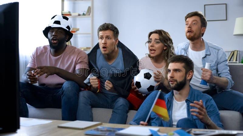 Mång--person som tillhör en etnisk minoritet tyska fans som sitter på soffan och håller ögonen på det modiga understödjande laget royaltyfria bilder