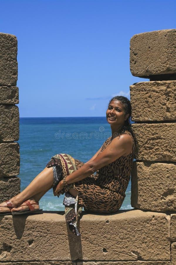 Mång--ras- flicka som ler vid havet arkivfoton