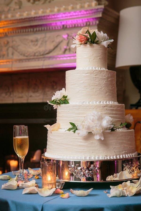 Mång- tiered bröllopstårta med vita blommor och kräm- glasyr på kaka på en tabell med stearinljus och champagneexponeringsglas -  royaltyfri foto