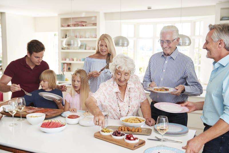Mång--utveckling familj och vänner som äter mat i kök på berömpartiet arkivfoto