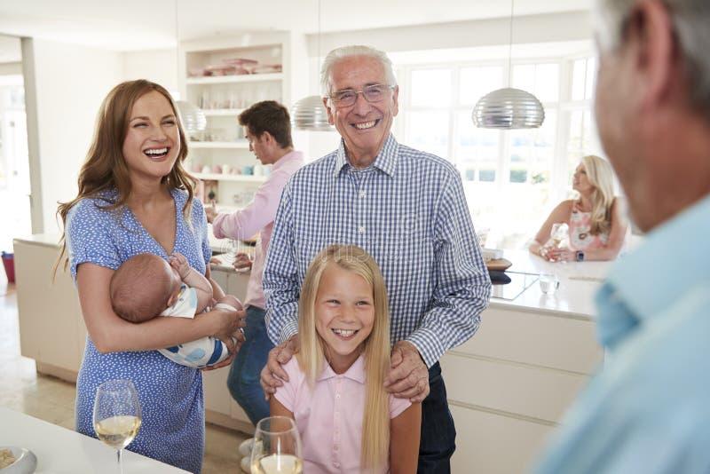 Mång--utveckling familj och vänner som samlar i kök för berömparti royaltyfria bilder