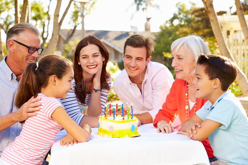 Mång--utveckling familj som firar födelsedag i trädgård arkivbild
