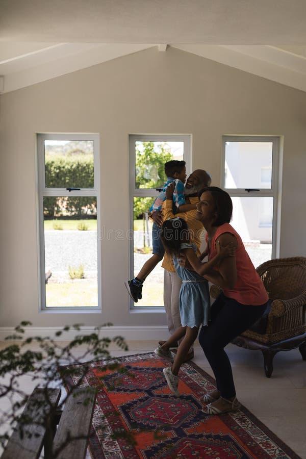 Mång--utveckling familj som har gyckel i vardagsrum arkivfoton