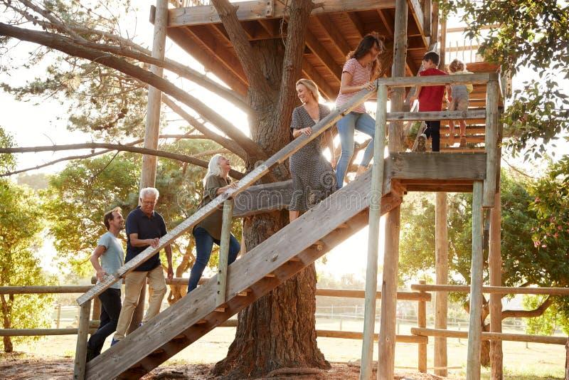Mång--utveckling familj som klättrar den utomhus- träplattformen till trädhuset i trädgård royaltyfria bilder
