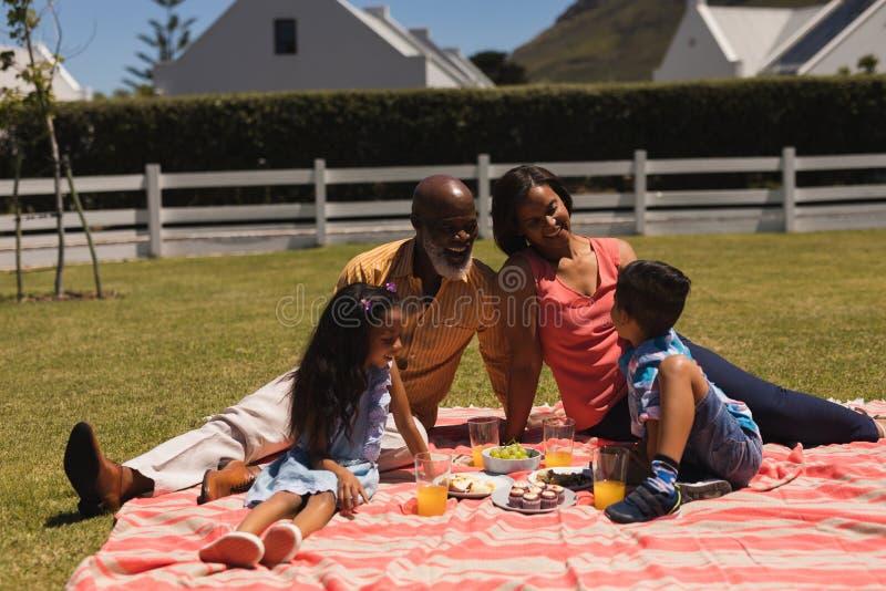Mång--utveckling familj som påverkar varandra och skrattar med de i trädgården royaltyfri bild