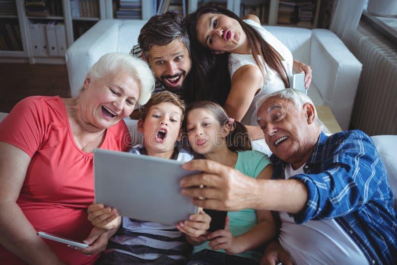 Mång--utveckling familj som tar en selfie på den digitala minnestavlan i vardagsrum royaltyfri bild
