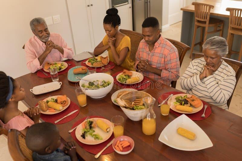 Mång--utveckling familj som tillsammans ber innan att ha mål royaltyfri fotografi