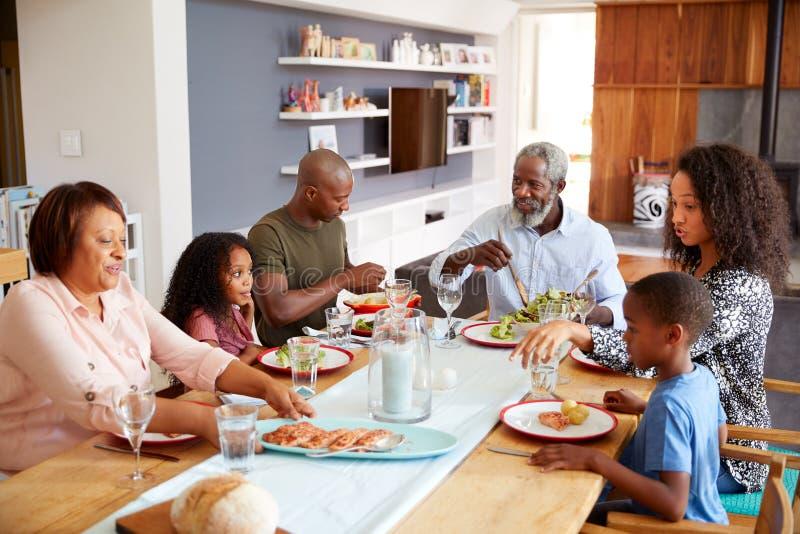 Mång--utveckling familj som tillsammans sitter runt om hemmastatt tyckande om mål för tabell royaltyfri bild