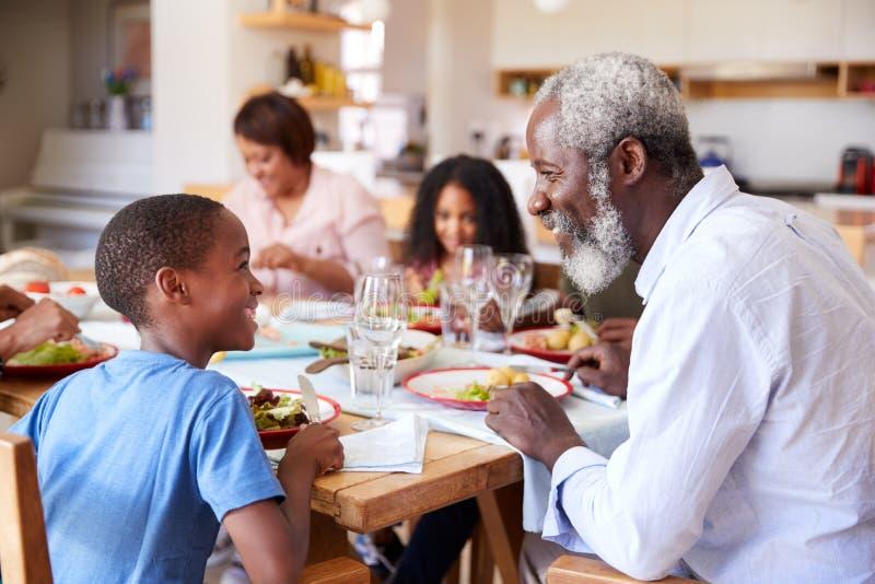 Mång--utveckling familj som tillsammans sitter runt om hemmastatt tyckande om mål för tabell arkivbilder