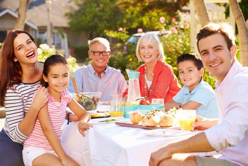 Mång--utveckling familj som tycker om utomhus- mål i trädgård royaltyfria bilder