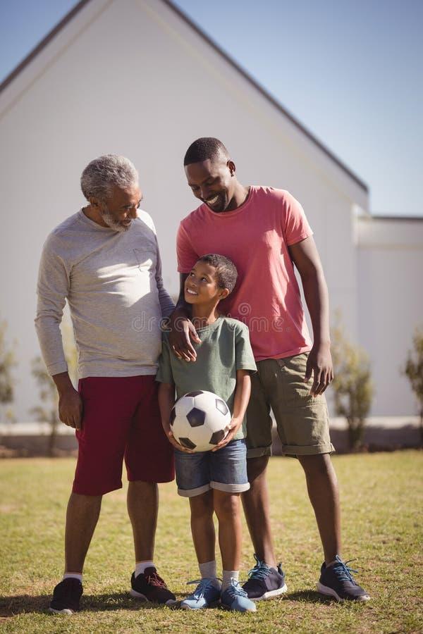 Mång--utveckling familjanseende i trädgård med fotboll royaltyfri bild