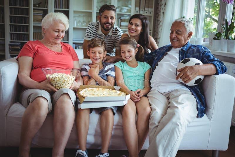 Mång--utveckling familjsammanträde med popcorn och pizza, medan hålla ögonen på fotbollsmatchen royaltyfri fotografi