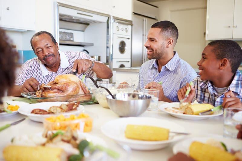 Mång--utveckling familjsammanträde runt om tabellen som äter mål royaltyfri foto