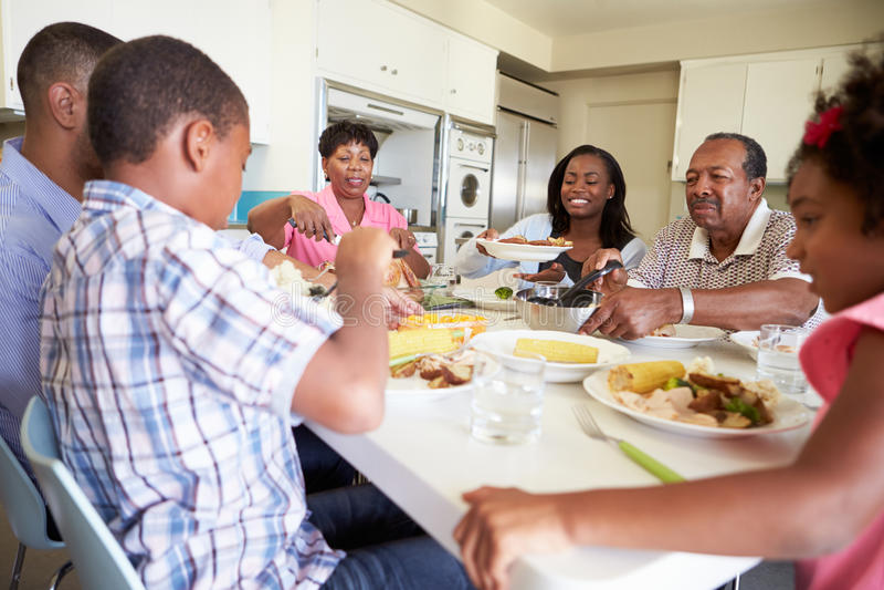 Mång--utveckling familjsammanträde runt om tabellen som äter mål royaltyfri fotografi