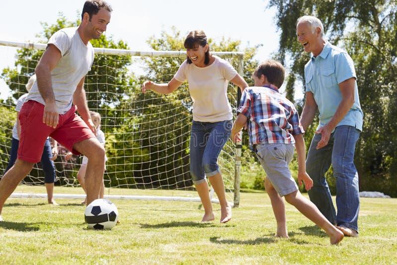 Mång- utveckling som spelar fotboll i trädgård tillsammans arkivfoton