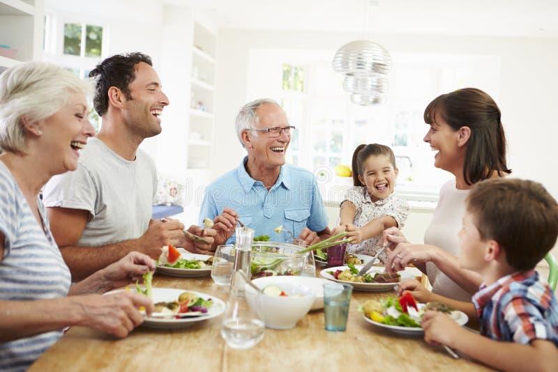 Mång- utvecklingsfamilj som äter mål runt om köksbordet arkivbild