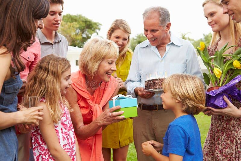 Mång- utvecklingsfamilj som firar födelsedag i trädgård arkivbilder