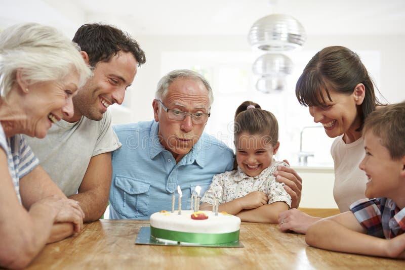 Mång- utvecklingsfamilj som firar farfars födelsedag arkivbilder