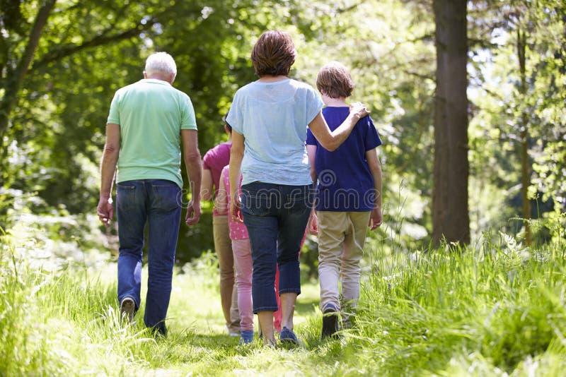 Mång- utvecklingsfamilj som går till och med sommarbygd arkivbilder