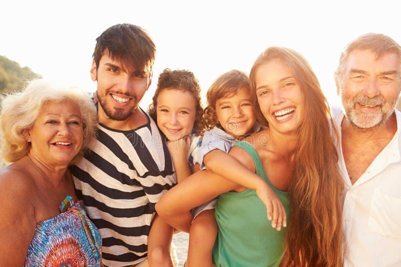 Mång- utvecklingsfamilj som ger barn ridturer på axlarna på ferie arkivfoton