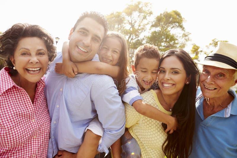 Mång- utvecklingsfamilj som har gyckel i trädgård tillsammans royaltyfri bild