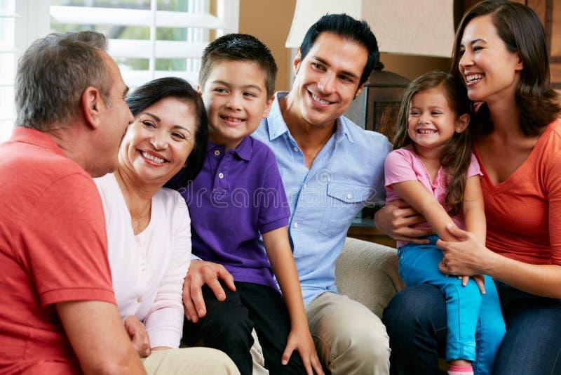 Mång- utvecklingsfamilj som hemma kopplar av tillsammans arkivfoton
