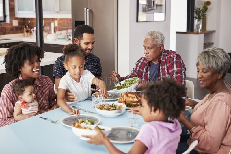 Mång- utvecklingsfamilj som hemma tycker om mål runt om tabellen royaltyfri fotografi