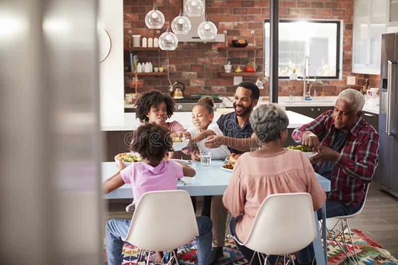 Mång- utvecklingsfamilj som hemma tycker om mål runt om tabellen arkivfoton