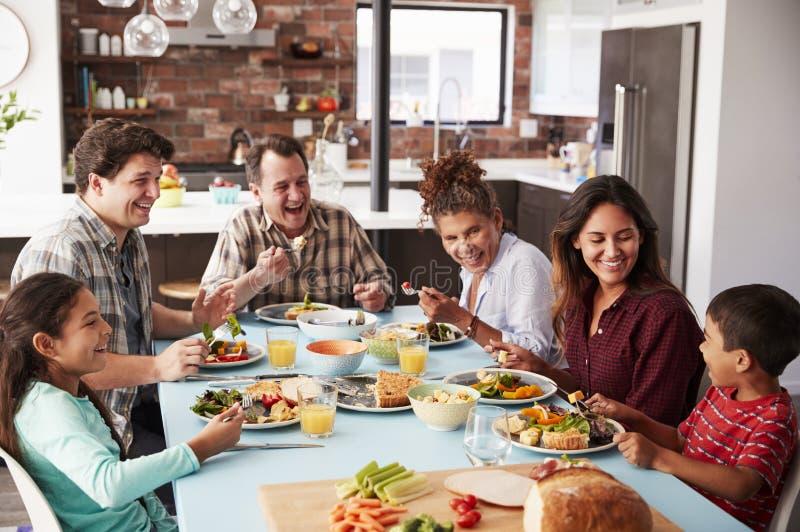 Mång- utvecklingsfamilj som hemma tycker om mål runt om tabellen tillsammans royaltyfri foto