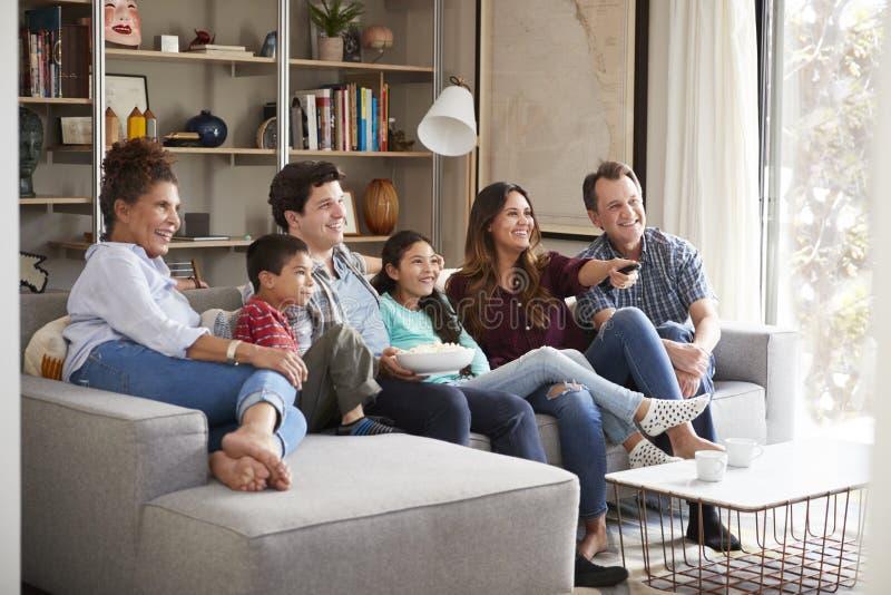 Mång- utvecklingsfamilj som kopplar av på Sofa At Home Watching Television royaltyfria foton