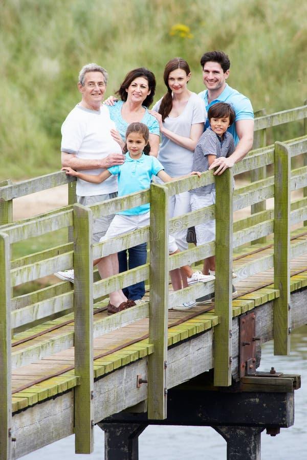 Mång- utvecklingsfamilj som promenerar träbron royaltyfri bild