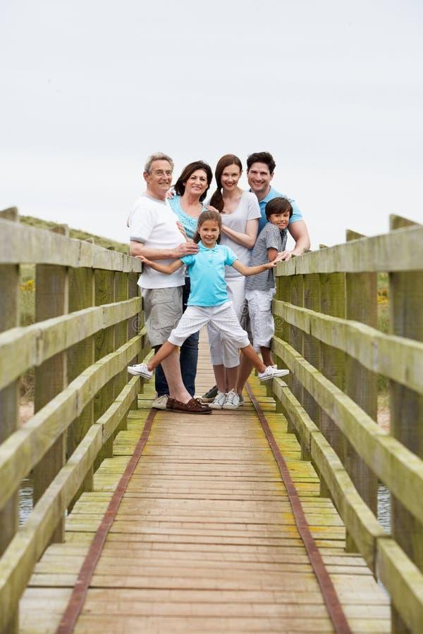 Mång- utvecklingsfamilj som promenerar träbron royaltyfria foton