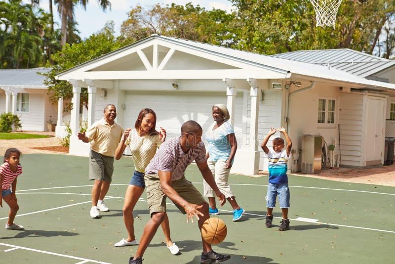 Mång- utvecklingsfamilj som spelar basket tillsammans royaltyfria bilder