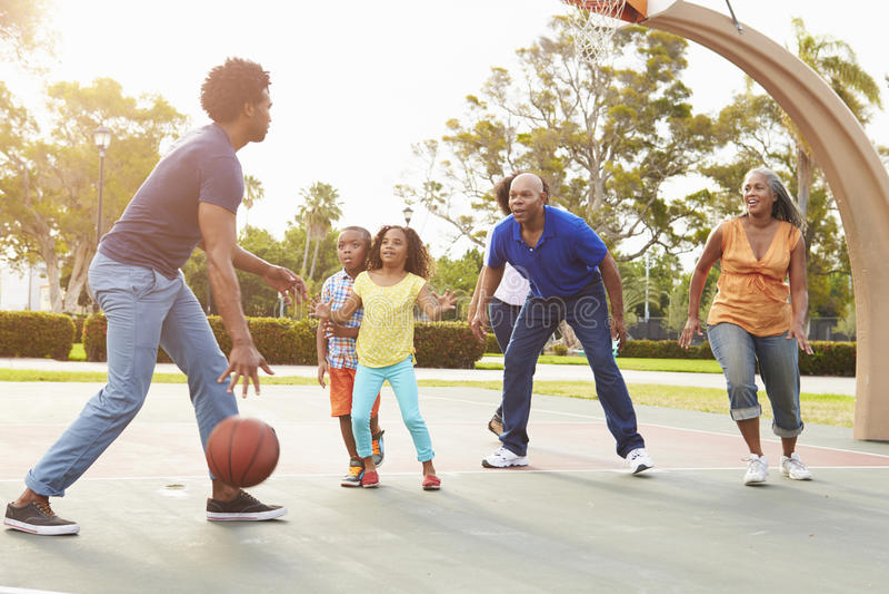 Mång- utvecklingsfamilj som spelar basket tillsammans royaltyfri bild