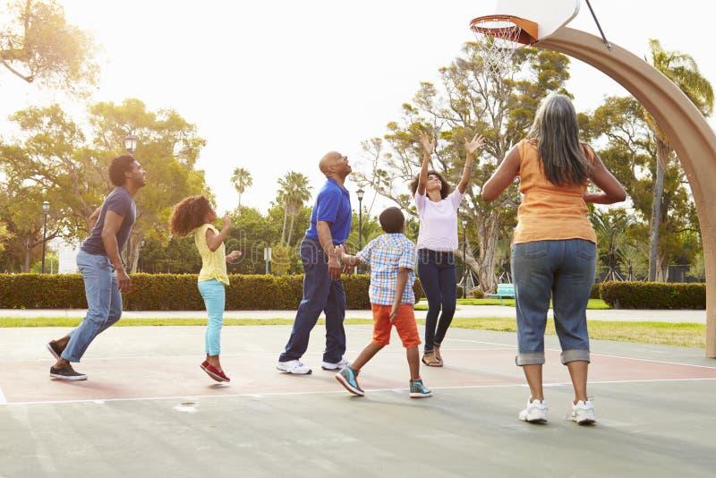 Mång- utvecklingsfamilj som spelar basket tillsammans royaltyfria foton