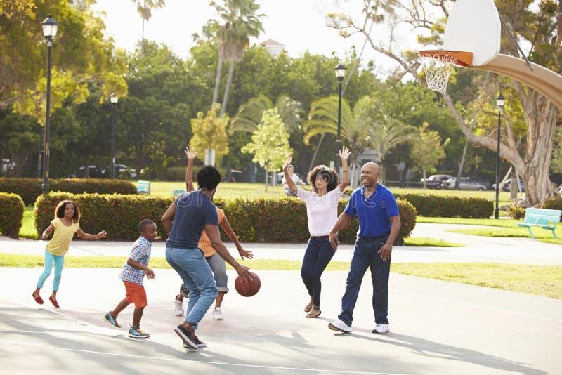 Mång- utvecklingsfamilj som spelar basket tillsammans arkivbild