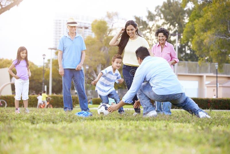Mång- utvecklingsfamilj som spelar fotboll tillsammans arkivbild
