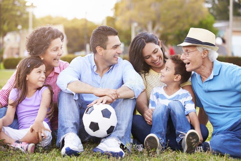 Mång- utvecklingsfamilj som spelar fotboll tillsammans arkivfoto