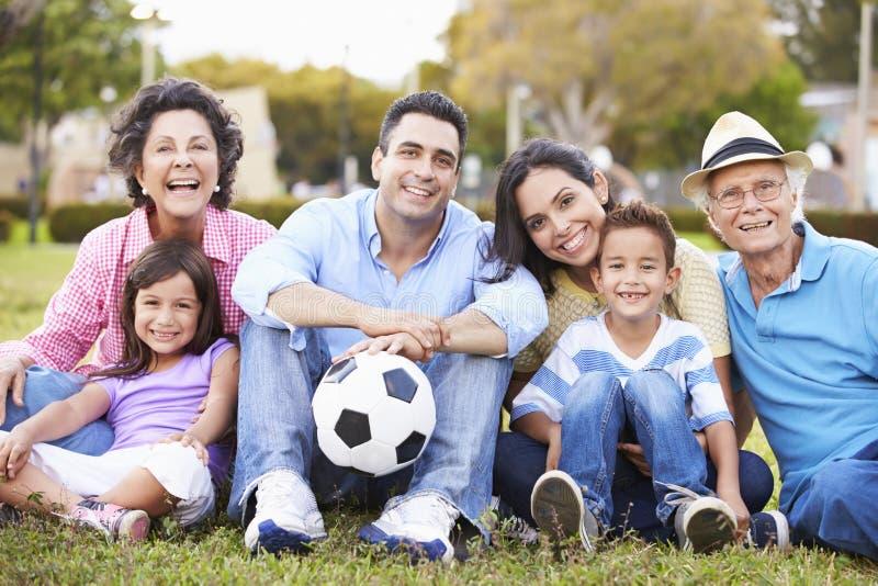Mång- utvecklingsfamilj som spelar fotboll tillsammans royaltyfria bilder