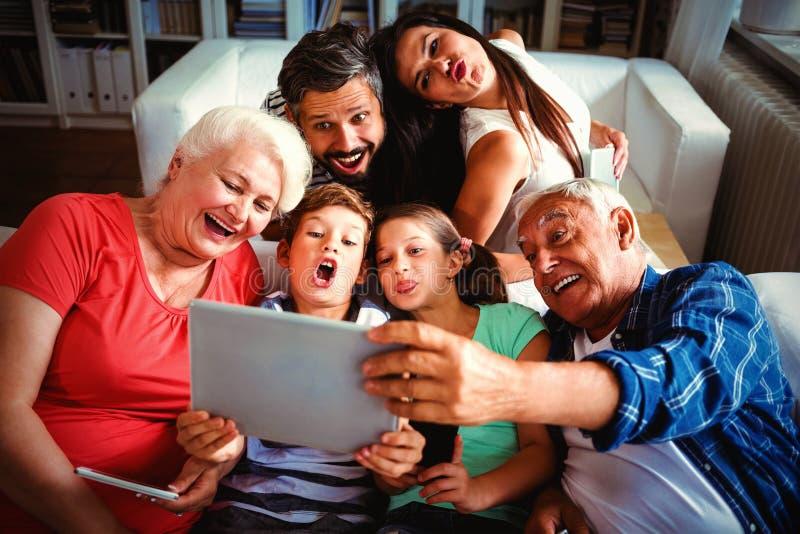 Mång- utvecklingsfamilj som tar en selfie på den digitala minnestavlan i vardagsrum royaltyfri foto