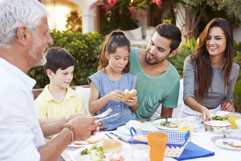 Mång- utvecklingsfamilj som tillsammans äter mål på det fria arkivfoton
