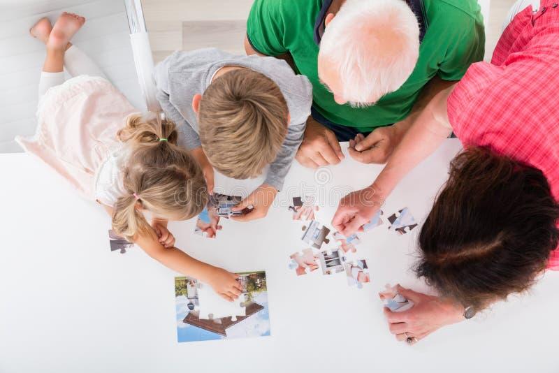 Mång- utvecklingsfamilj som tillsammans löser pusslet hemma royaltyfri foto