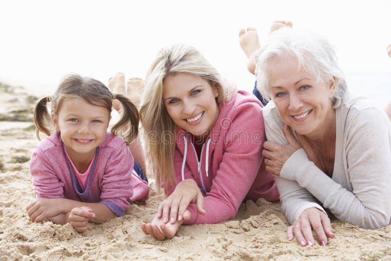 Mång- utvecklingsfamilj som tillsammans ligger på stranden royaltyfria foton
