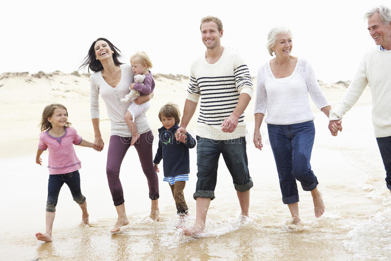 Mång- utvecklingsfamilj som tillsammans promenerar stranden royaltyfri bild