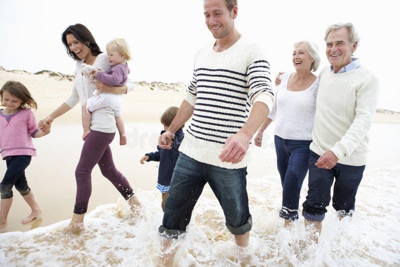 Mång- utvecklingsfamilj som tillsammans promenerar stranden arkivfoto